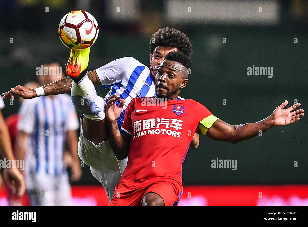 Brazilian football player Fernandinho Henrique, right, of Chongqing SWM passes the ball against Brazilian football player Junior Urso of Guangzhou R&F Stock Photo