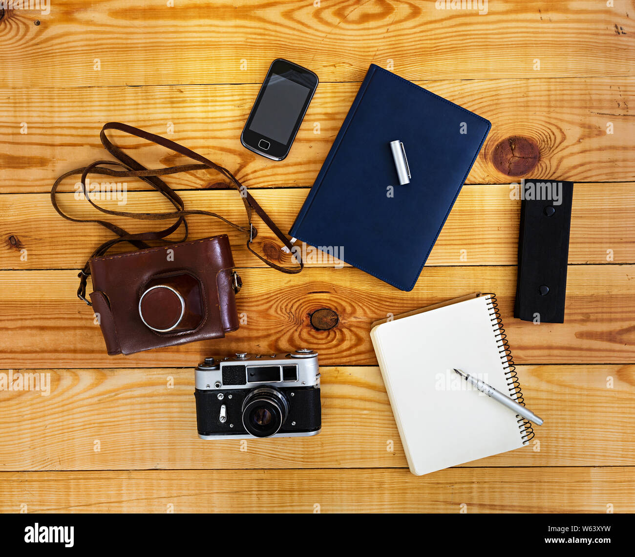 Flat lay, top view office table desk. Desk workspace with retro camera, diary, pen, case on wooden background. Stock Photo