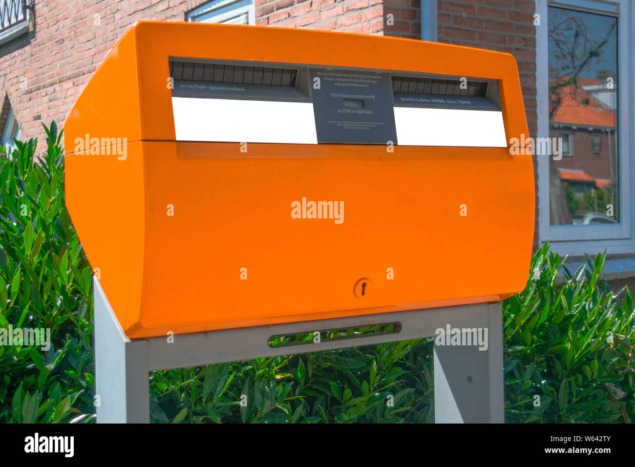 Posting a letter in the Netherlands - Orange Dutch letterbox Stock Photo