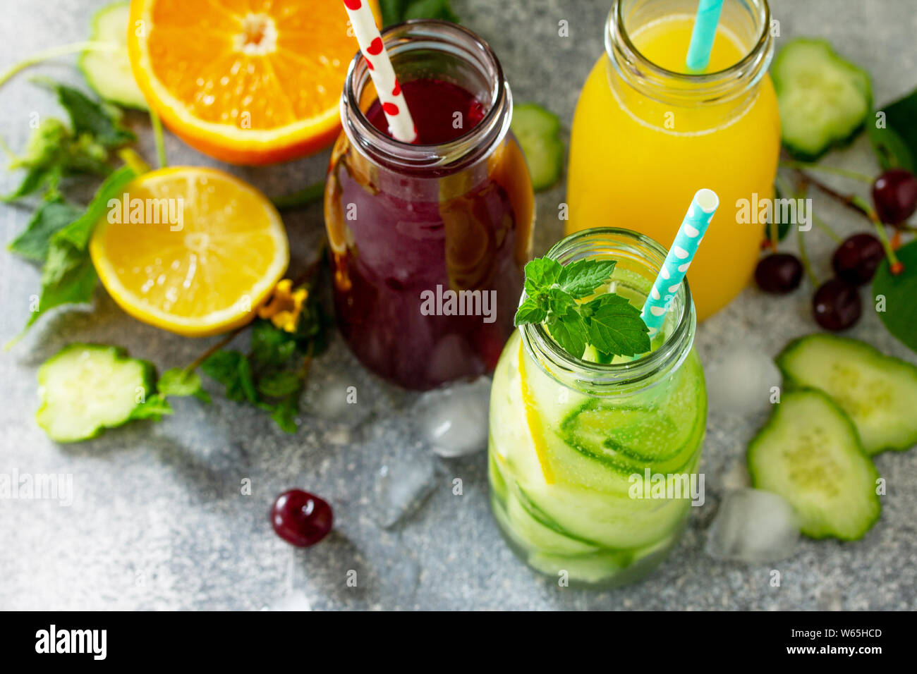 Various refreshments drinks - detox cucumber water, cherry juice and orange juice on stone table. Stock Photo