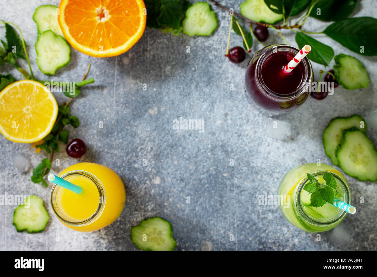 Various refreshments drinks - detox cucumber water, cherry juice and orange juice on stone table. Top view flat lay with copy space for your text. Stock Photo