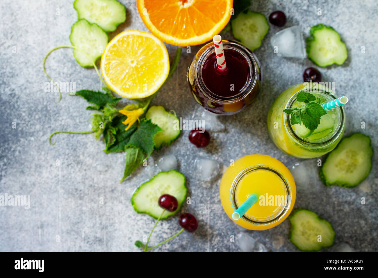 Various refreshments drinks - detox cucumber water, cherry juice and orange juice on stone table. Top view flat lay. Stock Photo