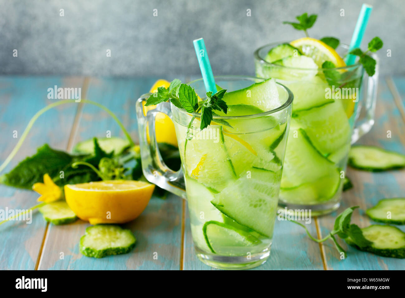 Glasses with fresh organic Cold and refreshing infused detox water with lemon and cucumber on wooden table. Copy space for your text. Stock Photo