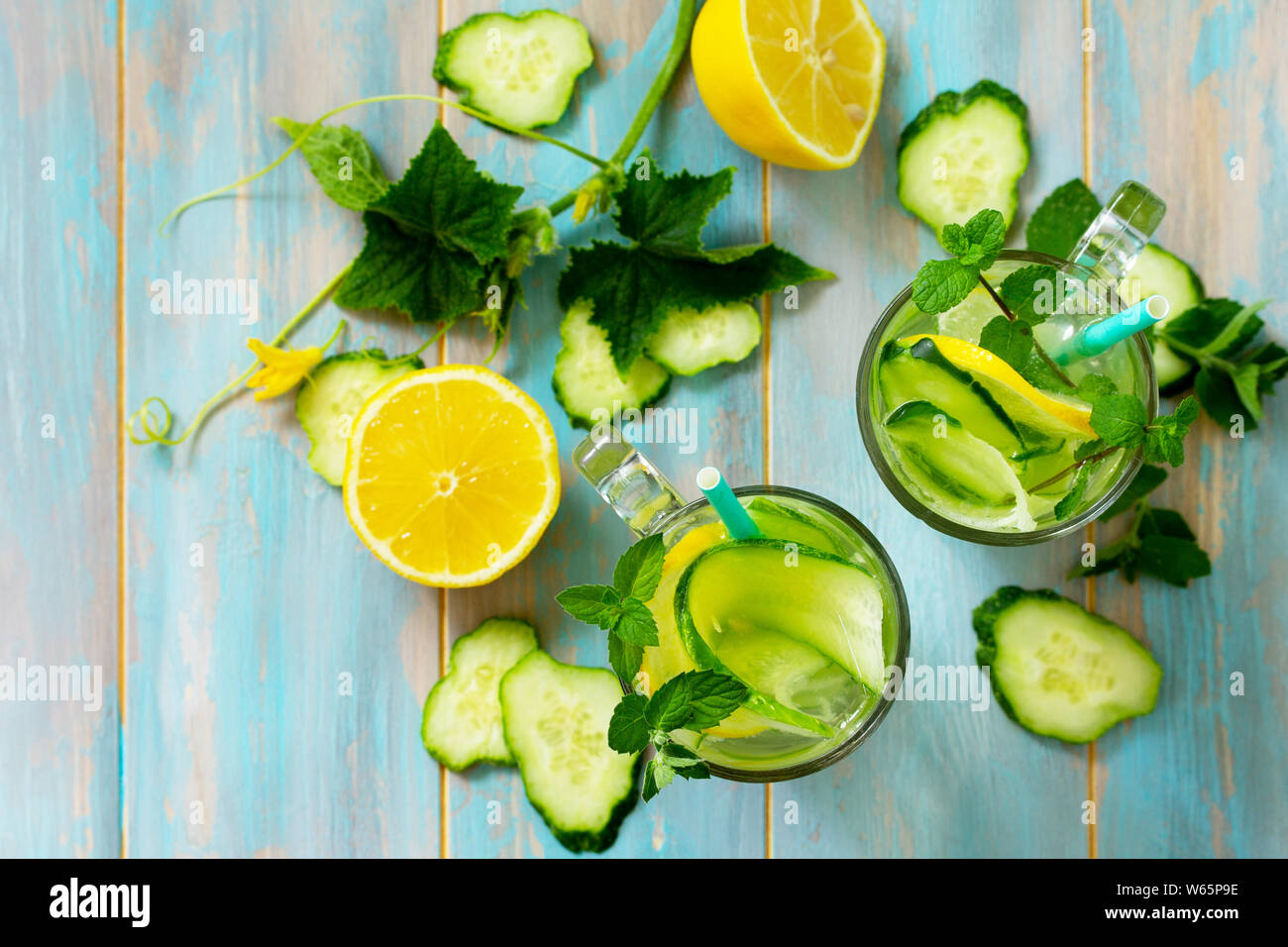 Glasses with fresh organic Cold and refreshing infused detox water with lemon and cucumber on wooden table. Top view flat lay. Stock Photo