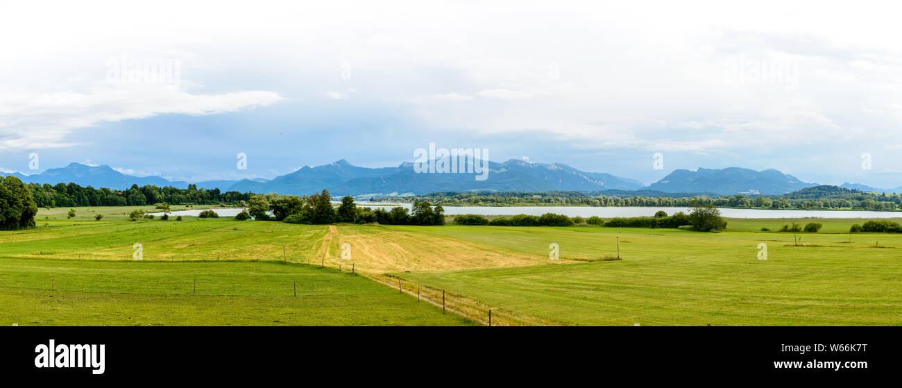 Panorama view on lake Chiemsee, alps mountains, cloudy sky, green fields, mountain Kampenwand. Bavaria, Bayern, Germany Stock Photo