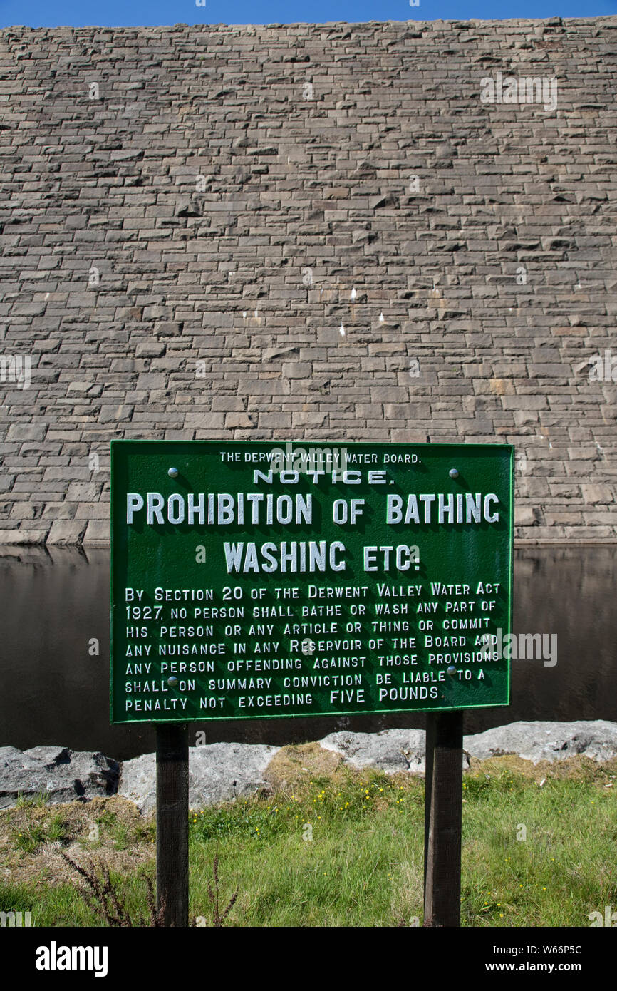 Pribition of bathing notice below the dam wall of Derwent Reservoir on the River Derwent in the Peak District National Park, on the border between Cou Stock Photo