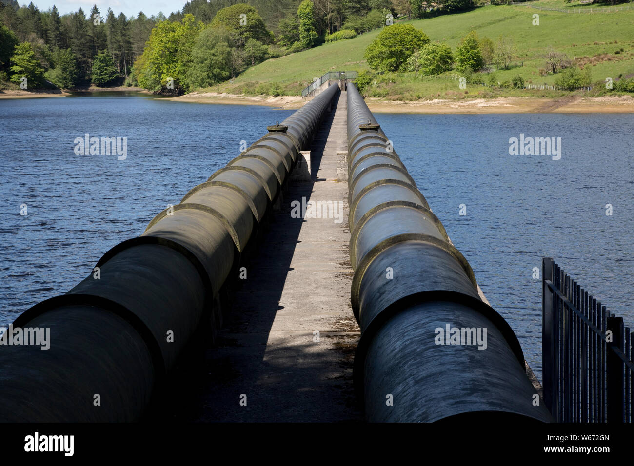 Twin pipe aqueducts at Ladybower Reservoir, the largest (holding 6300 million gallons) of three water storage reservoirs in the Derwent Valley, Peak D Stock Photo