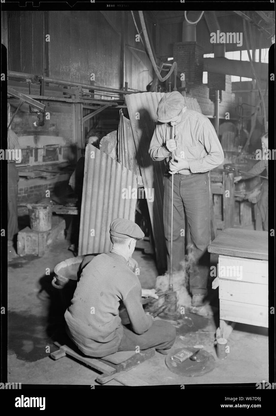 Millville, New Jersey - Glass bottles. T.C. Wheaton Co. The flint glass shop showing a blower rotating a bottle as he blows it in an iron mould. A mould boy is sitting on the floor. The blower takes the glass from the oven, puts in a mould and as he blows he slowly works it around in his hand. When the shutting mould boy opens the mould a second boy carries it away to be annealed. Stock Photo