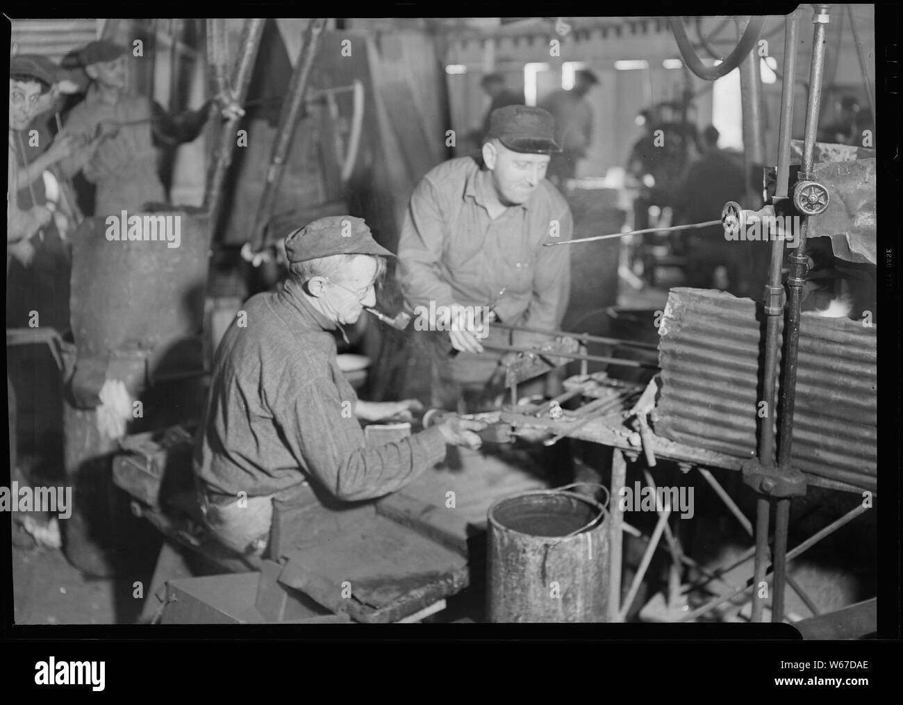 Millville, New Jersey - Glass bottles. T. C. Wheaton Co. A gaffer finishing a wide mouthed bottle. The man on the right takes the bottle from the blower on a rod and puts it on a gas flame, which may be seen behind the corrugated tin. When the neck of the bottle is re-heated to sufficient temperature, the gaffer on the left of this picture takes it over the fire and shapes it with iron tools by twirling it back and forth. The snapping-up boy then takes it over to be annealed. Stock Photo