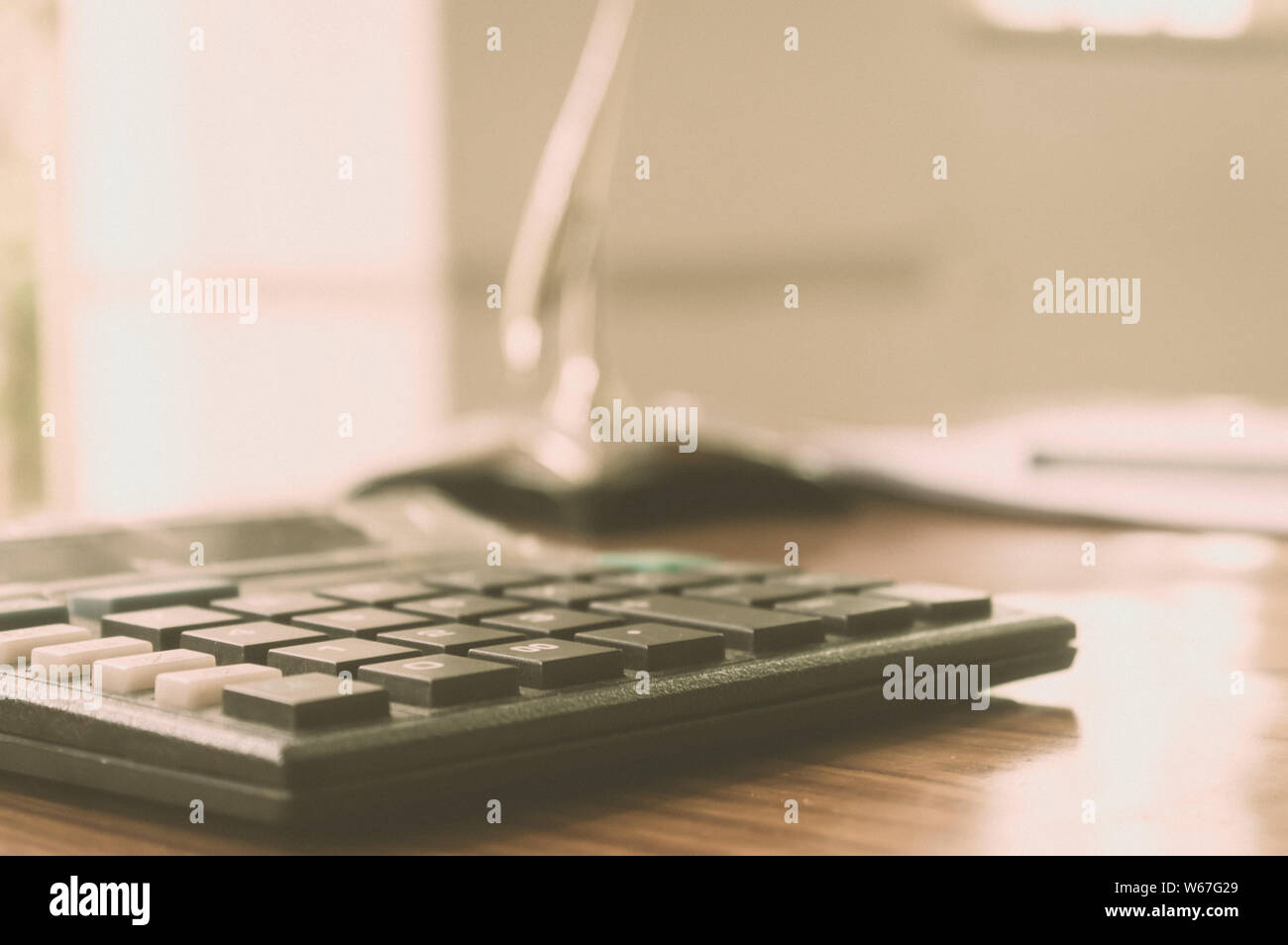 Close up of a calculator placed on office desk. A loan application form at a distance. Business Finance Concept. Vintage background. Isolated. Copy sp Stock Photo