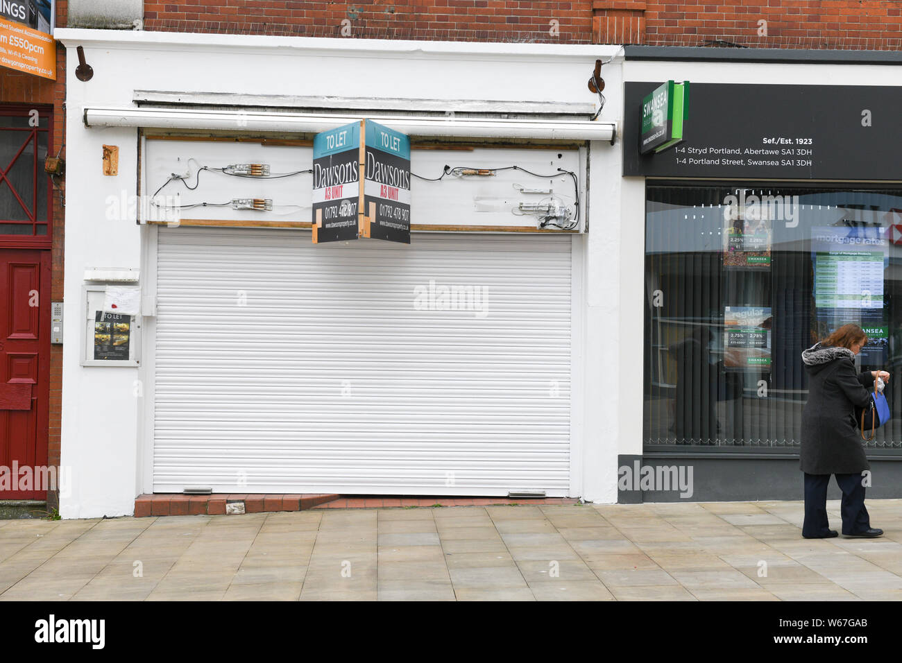 Shutters down over an empt and unused retail outlet on a UK high street. Thousands of shops are closing throughout the UK every week. Stock Photo