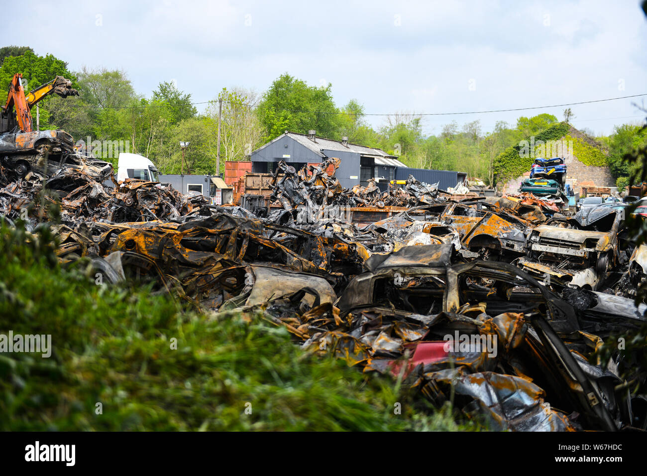 Piles of burnt cars are pictrured at a scrap yard in Ammanford, Wales, UK after a fire, leaving twisted and chard metal everywhere. Stock Photo