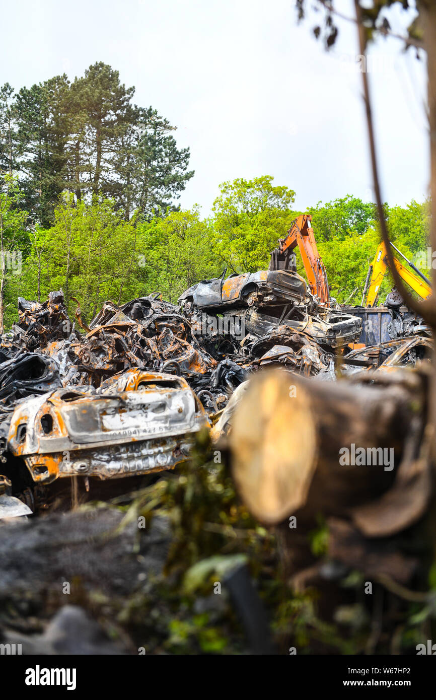 Piles of burnt cars are pictured at a scrap yard in Ammanford, Wales, UK after a fire, leaving twisted and chard metal everywhere. Stock Photo