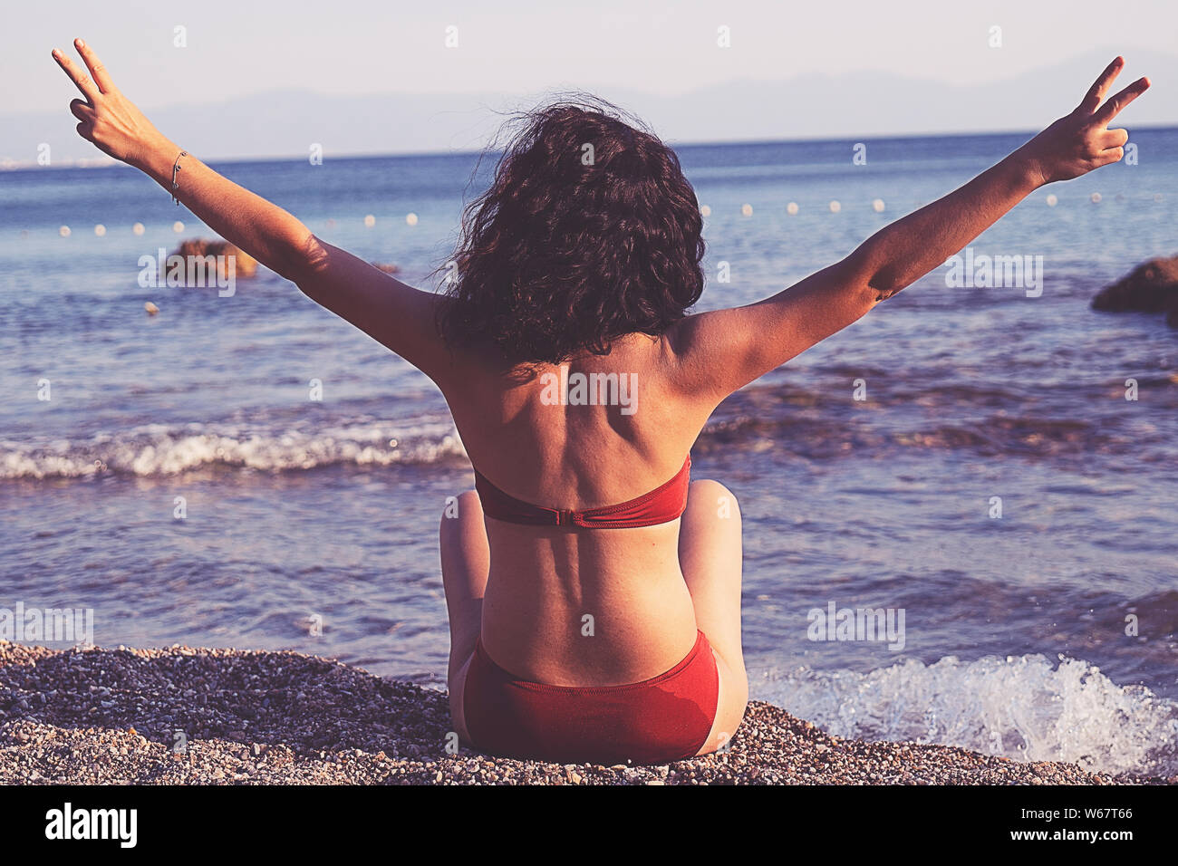 summer vacation, holidays, gesture, travel and people concept - young woman showing peace or victory sign on beach from back Stock Photo