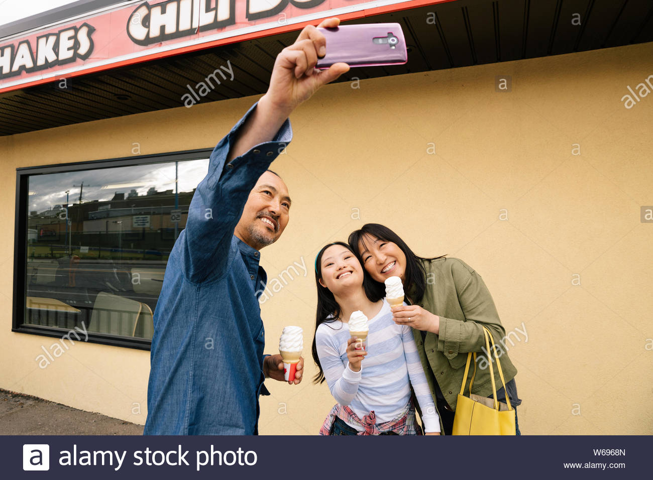 Family with camera phone taking selfie and eating ice cream outside drive-in Stock Photo