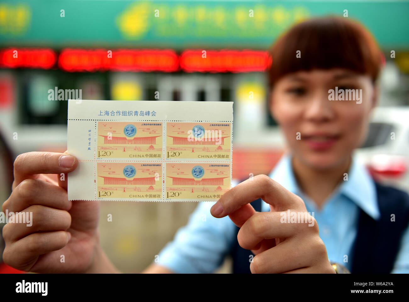 A Chinese employee shows a sheet of stamps commemorating the 18th Shanghai Cooperation Organization (SCO) summit at a China Post Office in Xinle city, Stock Photo