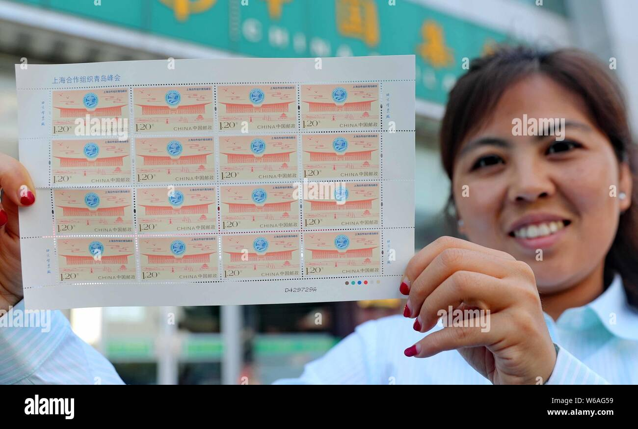 A Chinese employee shows a sheet of stamps commemorating the 18th Shanghai Cooperation Organization (SCO) summit at a China Post Office in Qinhuangdao Stock Photo