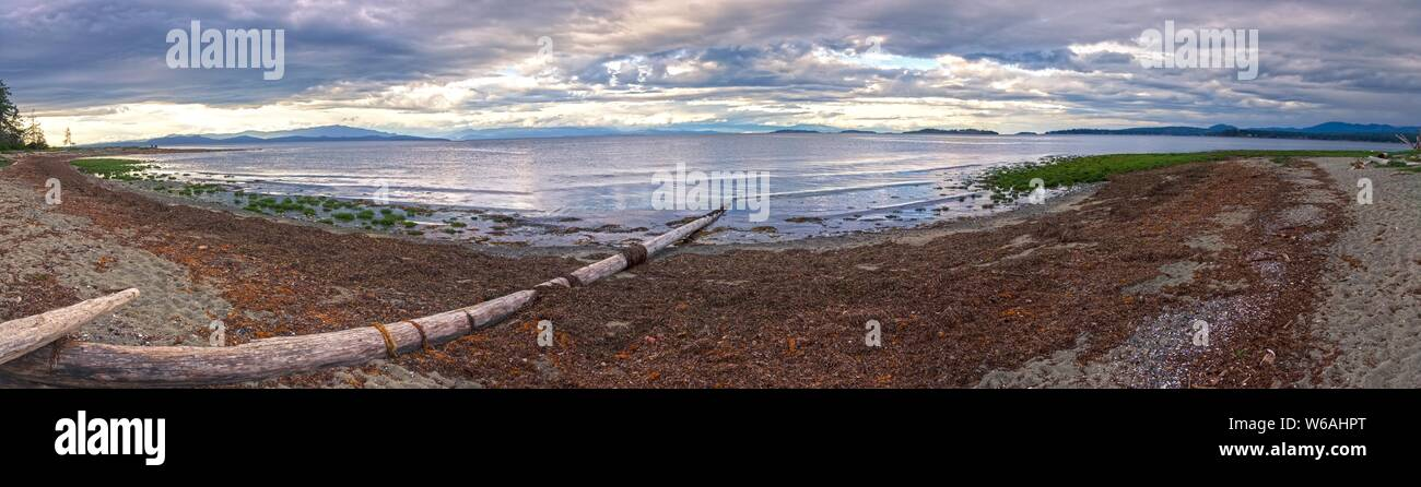 Wide Panoramic Scenic Landscape View of Rathtrevor Beach Provincial Park on Vancouver Island and Dramatic Sunset Sky over Strait of Georgia, BC Canada Stock Photo