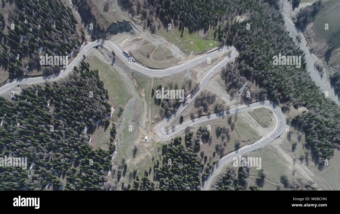 Aerial view of a winding mountain road with 18 curves around the Tian Shan, also known as the Tengri Tagh, mountain in Hami city, northwest China's Xi Stock Photo