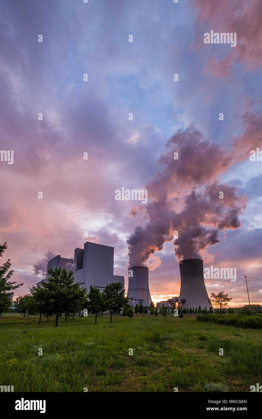The buildings and steaming cooling towers of a coal-fired power plant in agricultural landscape at sunset Stock Photo