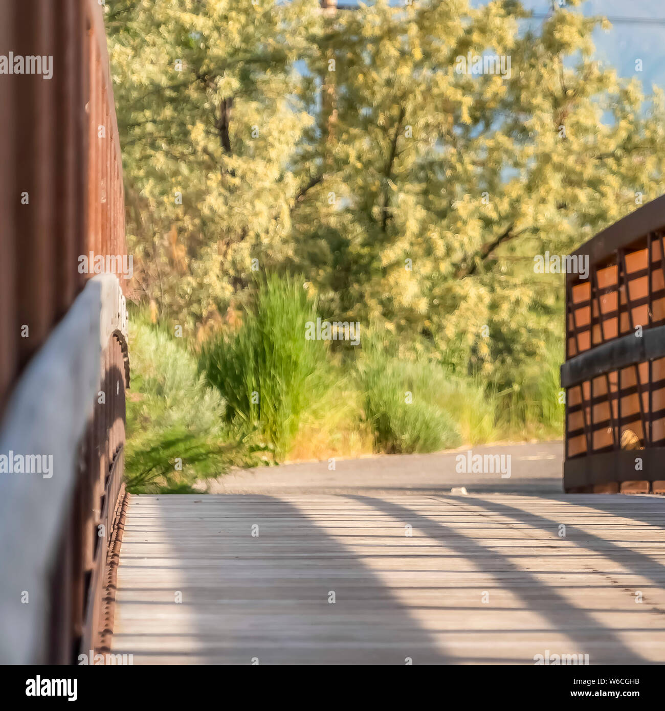 Square Close up of a bridge with metal guardrail and wood deck on a sunny day Stock Photo
