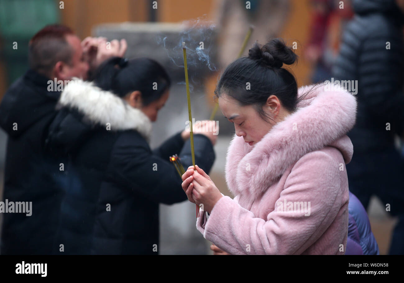 FILE--A Chinese worshipper burns incense sticks to pray for