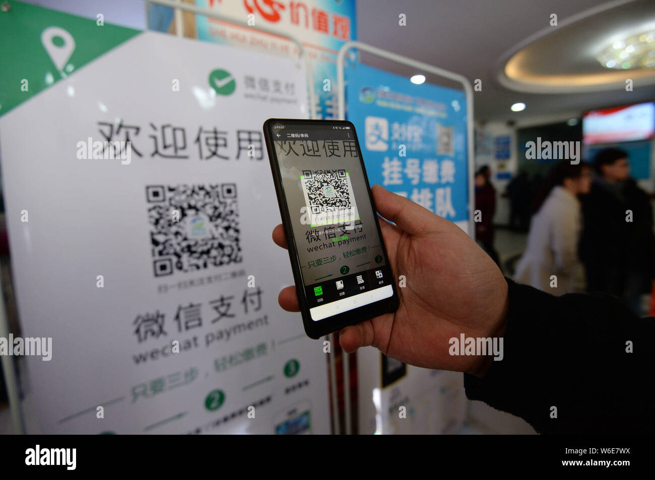 FILE--A patient uses his smartphone to scan the QR code of