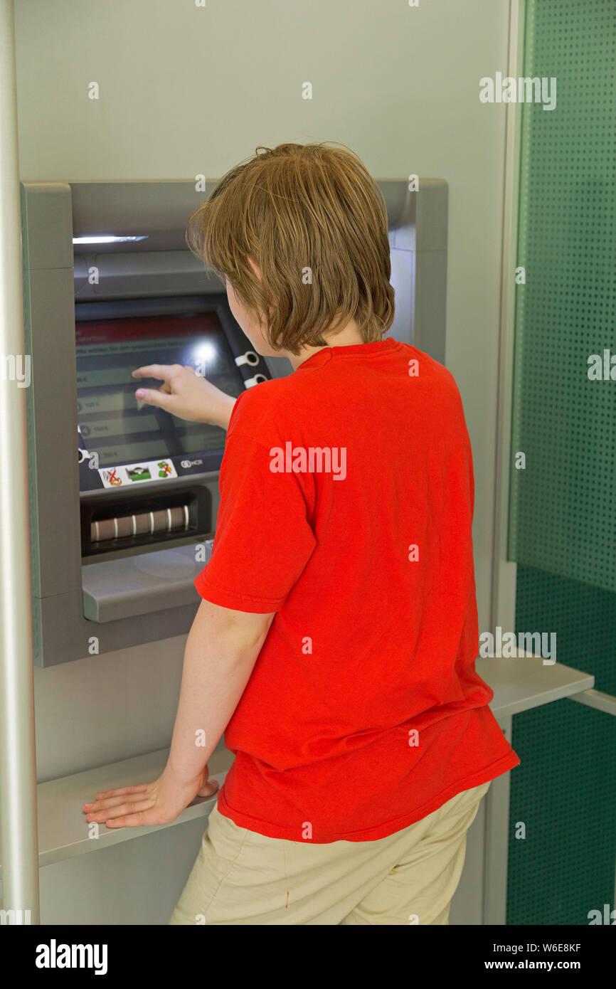 boy withdrawing money from a cash machine, Freyung, Bayerischer Wald, Bavaria, Germany Stock Photo