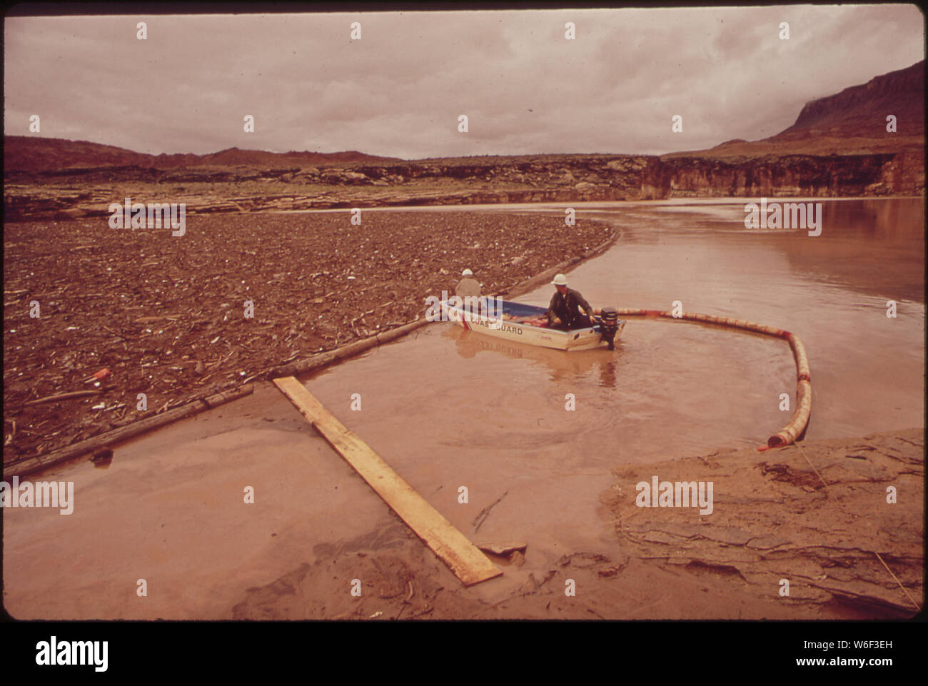 AT SITE OF OIL-SPILL CLEAN-UP OPERATIONS IN A REMOTE AREA OF THE SAN JUAN RIVER. BOAT PUSHES OIL-LADEN DEBRIS TO A POINT WHERE A DRAGLINE SHOVEL CAN REACH IT. SPILL ORIGINATED NEAR SHIPROCK, NEW MEXICO. OIL FLOWED 200 MILES DOWNSTREAM UNTIL TEMPORARILY CONTAINED BY THE LOG BOOM PICTURED HERE. JUST BEYOND BOOM SITE IS THE NORTHEASTERN TIP OF LAKE POWELL Stock Photo