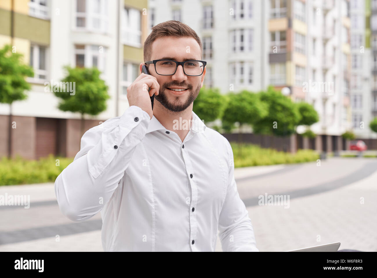 Close up of young, stylish, bearded man talking by phone on background of modern city with multistory houses. Positive businessman in glasses wearing in white shirt looking at camera. Stock Photo