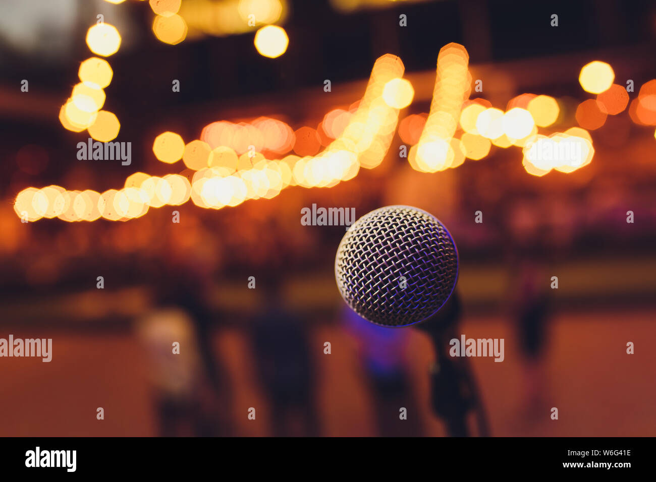 microphone on a stand up comedy stage with colorful bokeh , high contrast image. Stock Photo