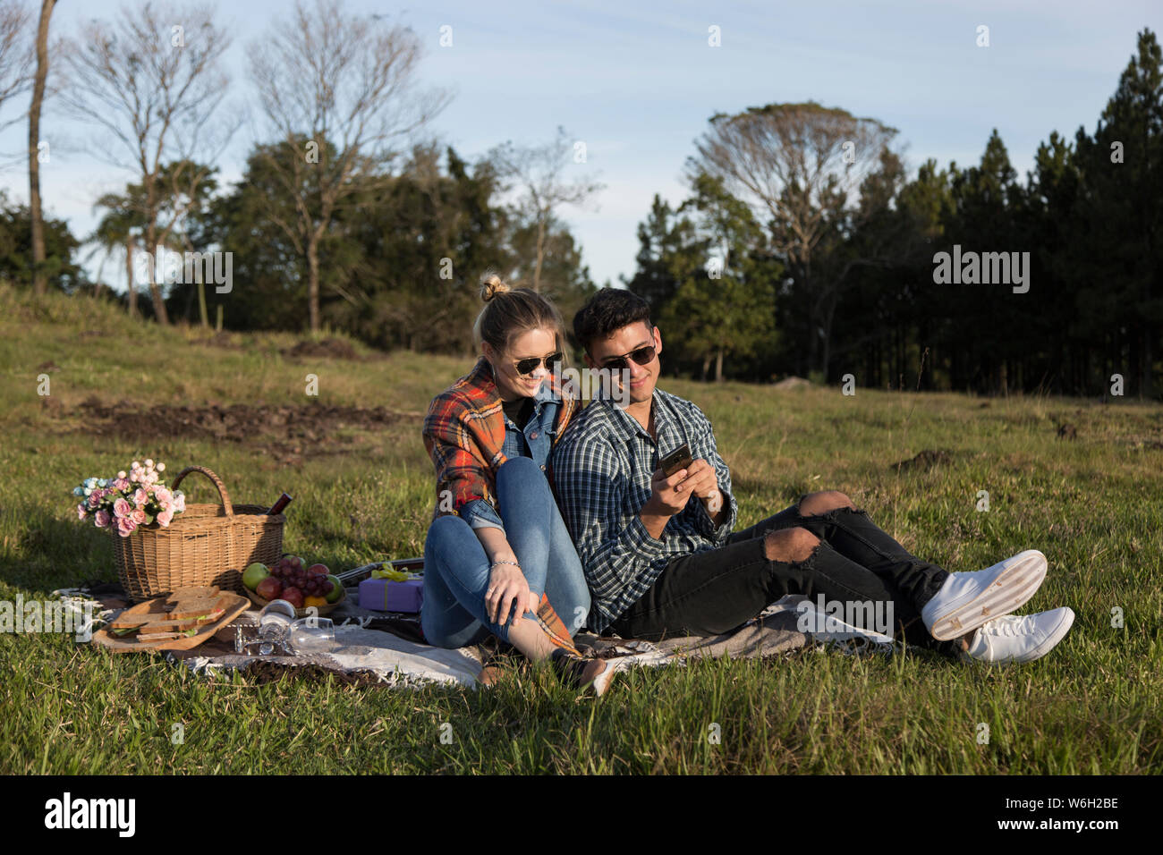 man and woman sitting with glasses taking selfies under the sun Stock Photo