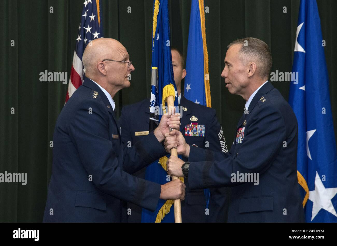 Maj. Gen. Tom Wilcox receives the unit flag from Gen. Arnold W. Bunch Jr. commander of Air Force Materiel Command, to become commander of the Air Force Installation and Mission Support Center July 25 during a ceremony at Joint Base San Antonio-Lackland, July 25, 2019. (U.S. Air Force photo by Johnny Saldivar). () Stock Photo
