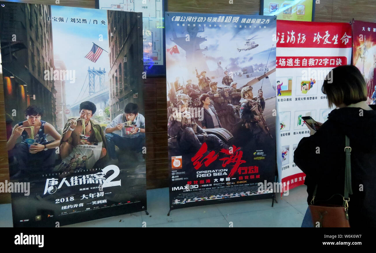 A Chinese Filmgoer Stands Next To Posters Of The Movies Detective Chinatown 2 Left And Operation Red Sea On The Second Day Of The Chinese Lunar Stock Photo Alamy
