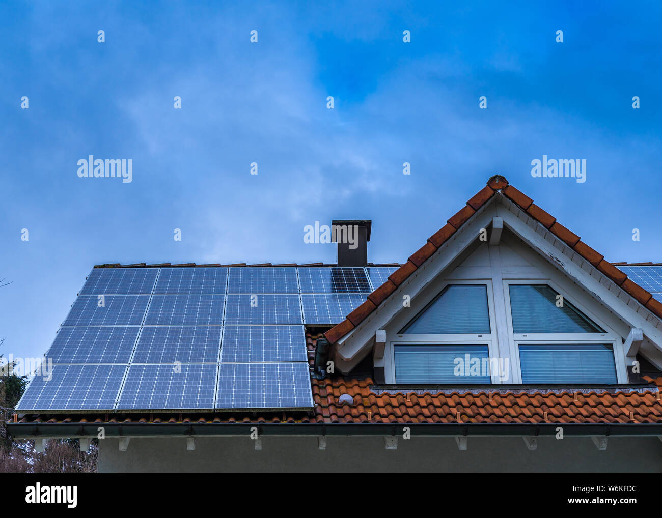 Red tile house roof coveredy by solar panels Stock Photo