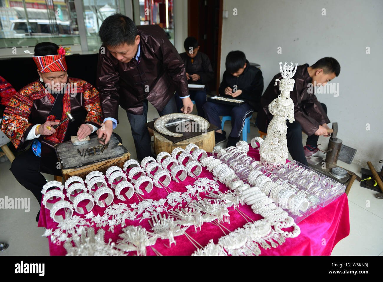 Chinese craftsmen make traditional silver decorations of
