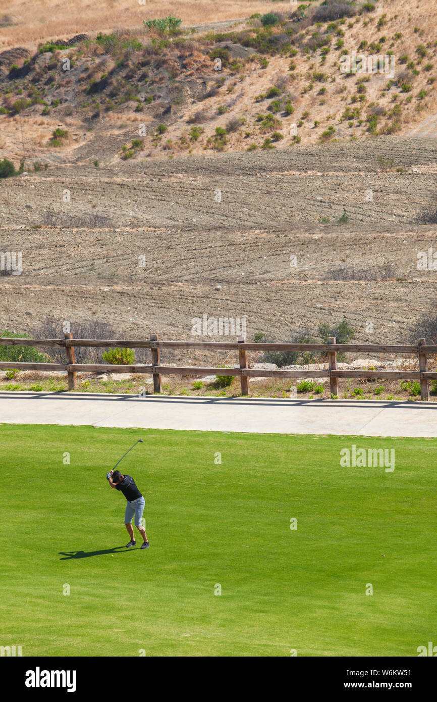 Golfer playing close to semi-arid environment. Golf courses sustainability concept Stock Photo