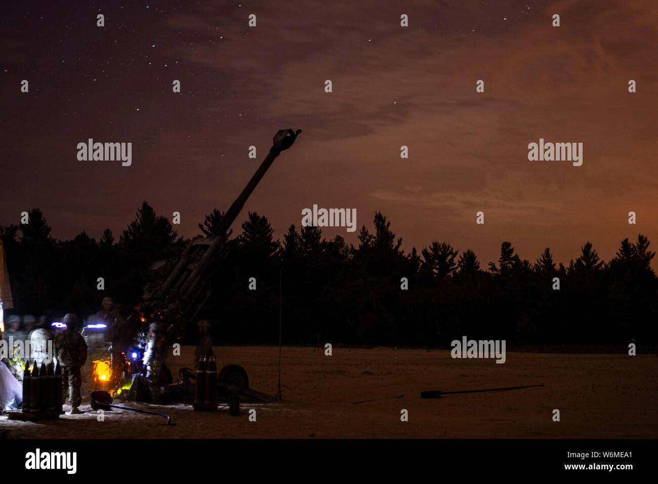 Soldiers assigned to the 1st Battalion, 258th Field Artillery of the New York Army National Guard conduct night fire training with the M-777A2 howtizer at Fort Drum, New York during their annual training on July 30, 2019. ( U.S. Army National Guard photo by Sgt. Matthew Gunther) Stock Photo