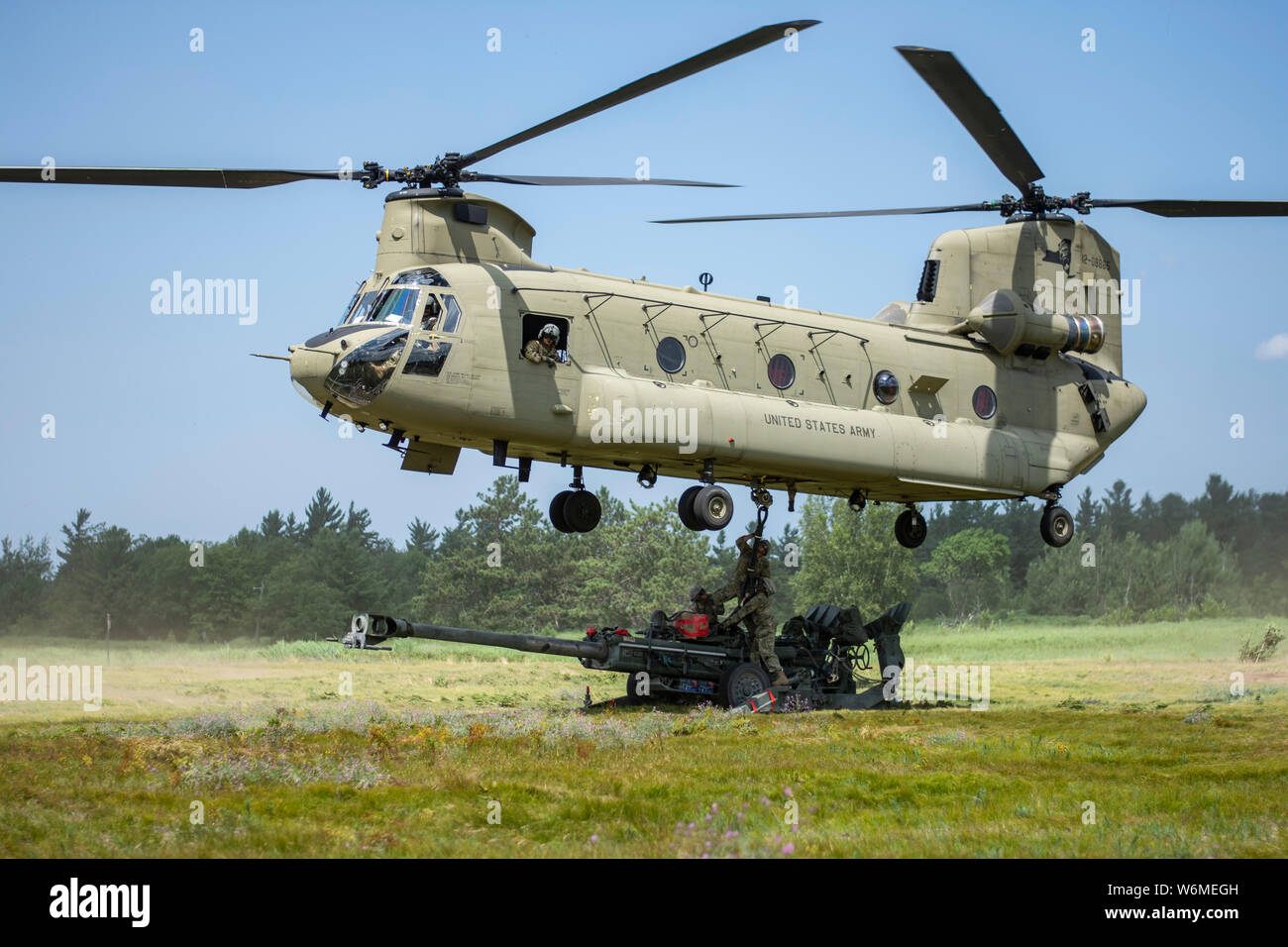 Soldiers of the 1st Battalion, 258th Field Artillery of the New York Army National Guard attach and M-777A2 howitzer to a CH-47 flown by the New York Army National Guard's Bravo Company, 3rd Battalion, 126th Aviation at Fort Drum, N.Y. on July 27, 2019. The 1st Battalion, 258th Field Artillery Soldiers were conducting live fire training and other exercises at Fort Drum as part of their two week annual training. ( U.S. Army National Guard photo by Sgt. Matthew Gunther) Stock Photo