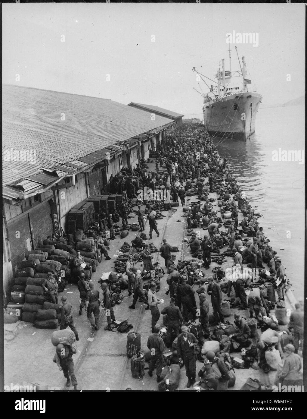 U.S. troops are pictured on pier after debarking from ship, somewhere in Korea.; General notes:  Use War and Conflict Number 1382 when ordering a reproduction or requesting information about this image. Stock Photo