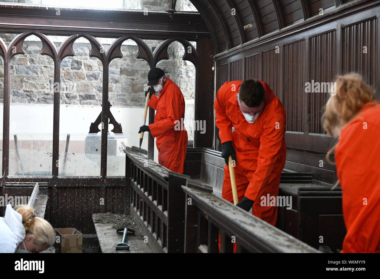 People is health and safety personal protection masks clean-up of St David's Church in Carmarthen , which is covered in pigeon droppings. Stock Photo