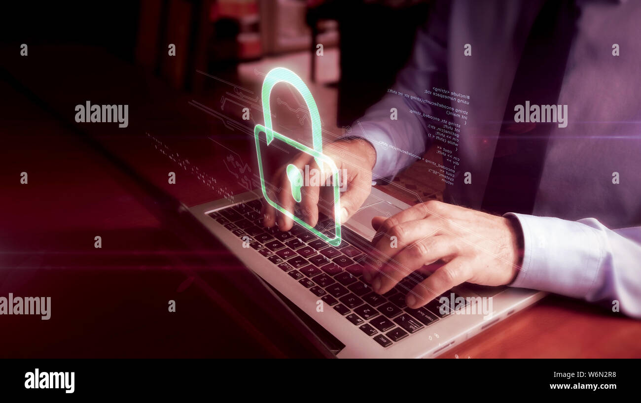 Man typing on laptop with padlock hologram screen over keyboard. Cyber security, computer protection and internet safety concept. Stock Photo