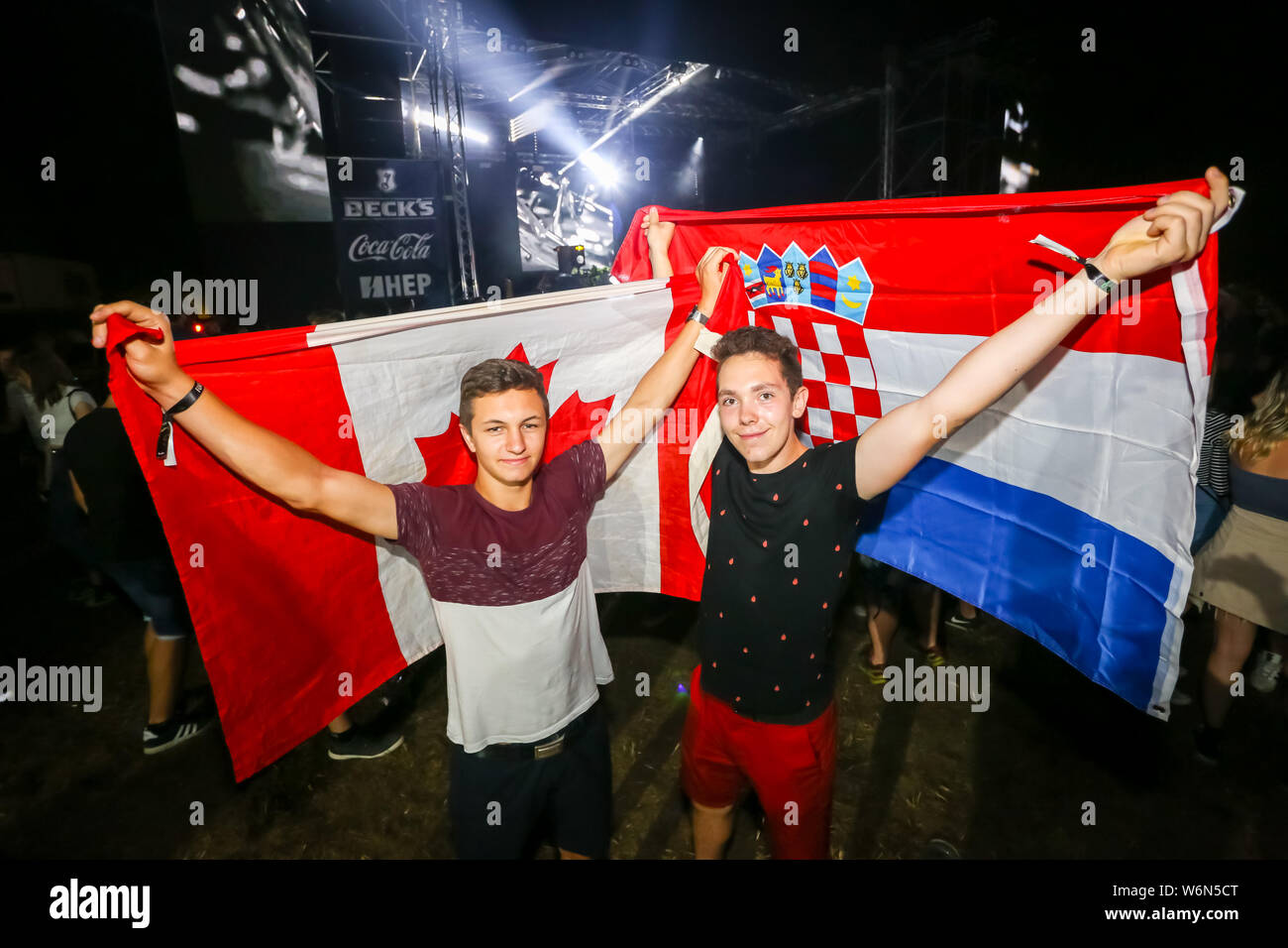 Brezje, Croatia - 20th July, 2019 : Two guys with a Canadian and Croatian flag posing on the Forestland, ultimate forest electronic music festival loc Stock Photo