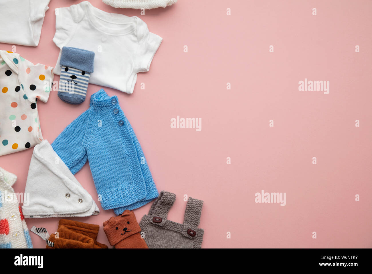 Cute Baby Clothes Layout On A Pastel Pink Background Stock Photo