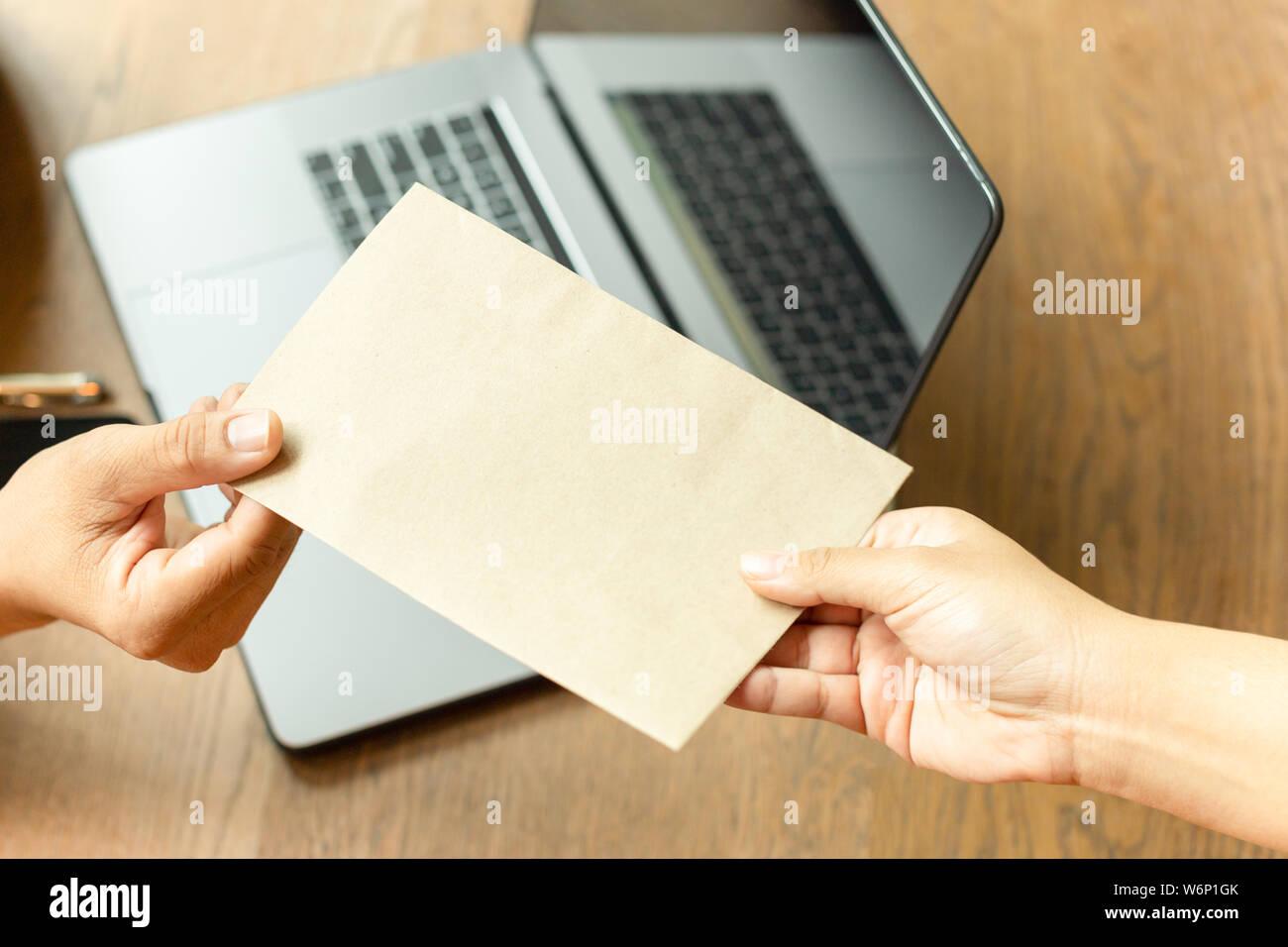 Businessman taking bribe money in brown envelope from partner. Stock Photo