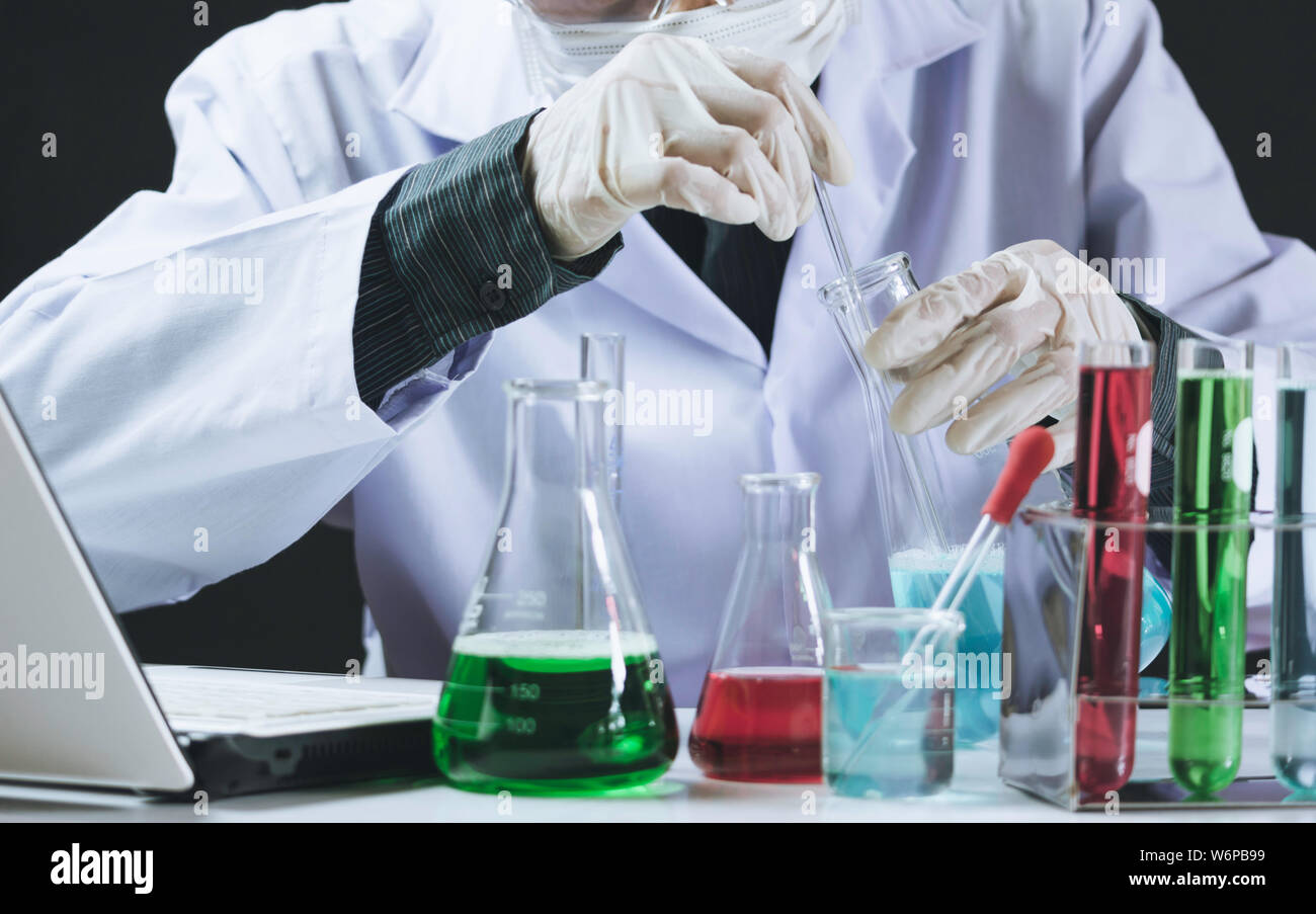Researcher with glass laboratory chemical test tubes with liquid for analytical , medical, pharmaceutical and scientific research concept. Stock Photo
