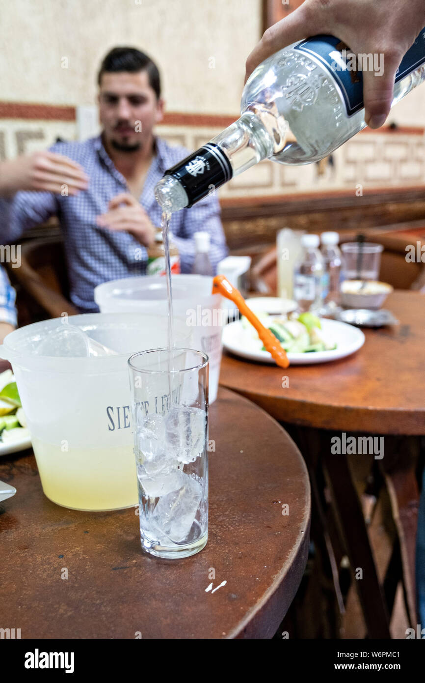 A waiter serves Siete Leguas blanco tequila at the Fellos Bar in Atotonilco de Alto, Jalisco, Mexico. The bar has been a meeting place for tequila distillery owners and workers for more than 50-years in the tiny mountain town of Atotonilco de Alto, home to Siete Leguas, Don Julio and Patron tequila brands. Stock Photo