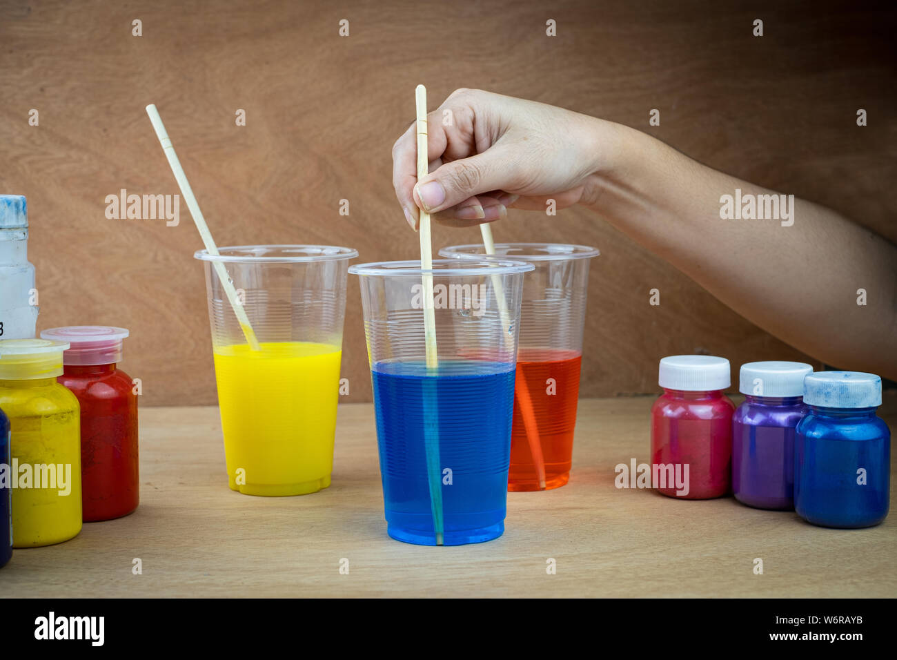Mixing color epoxy resin in plastic cup for casting Stabilizing wood