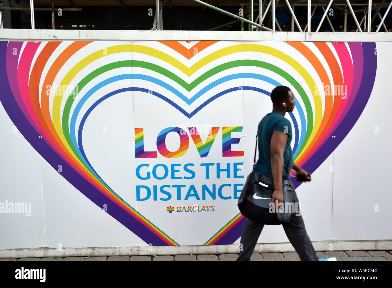 A man walks past a rainbow themed 'Love Goes the Distance