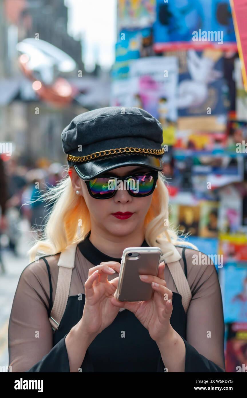 Edinburgh, Scotland, UK. 2nd August, 2019. A girl on the Royal Mile checking her mobile phone at the start of the Edinburgh Fringe Festival. Credit: Skully/Alamy Live News Stock Photo